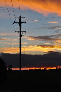 Power lines silhouette against the setting sun
